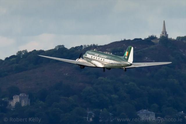 A Douglas DC3 flies past Manderley Castle and the Killiney Obelisk