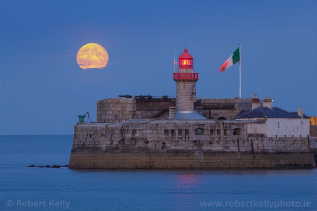 The full moon rises over the East pier lighthouse, Dun Laoghaire Harbour, County Dublin