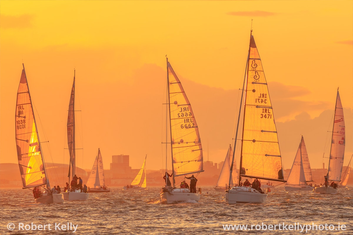Sailboats entering Dun Laoghaire Harbour at sunset