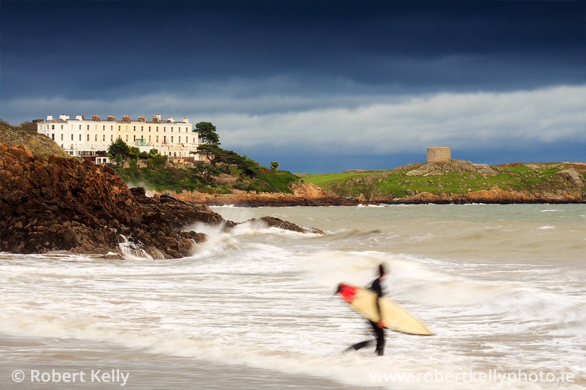 A surfer enters the water at Whiterock Beach, Dalkey